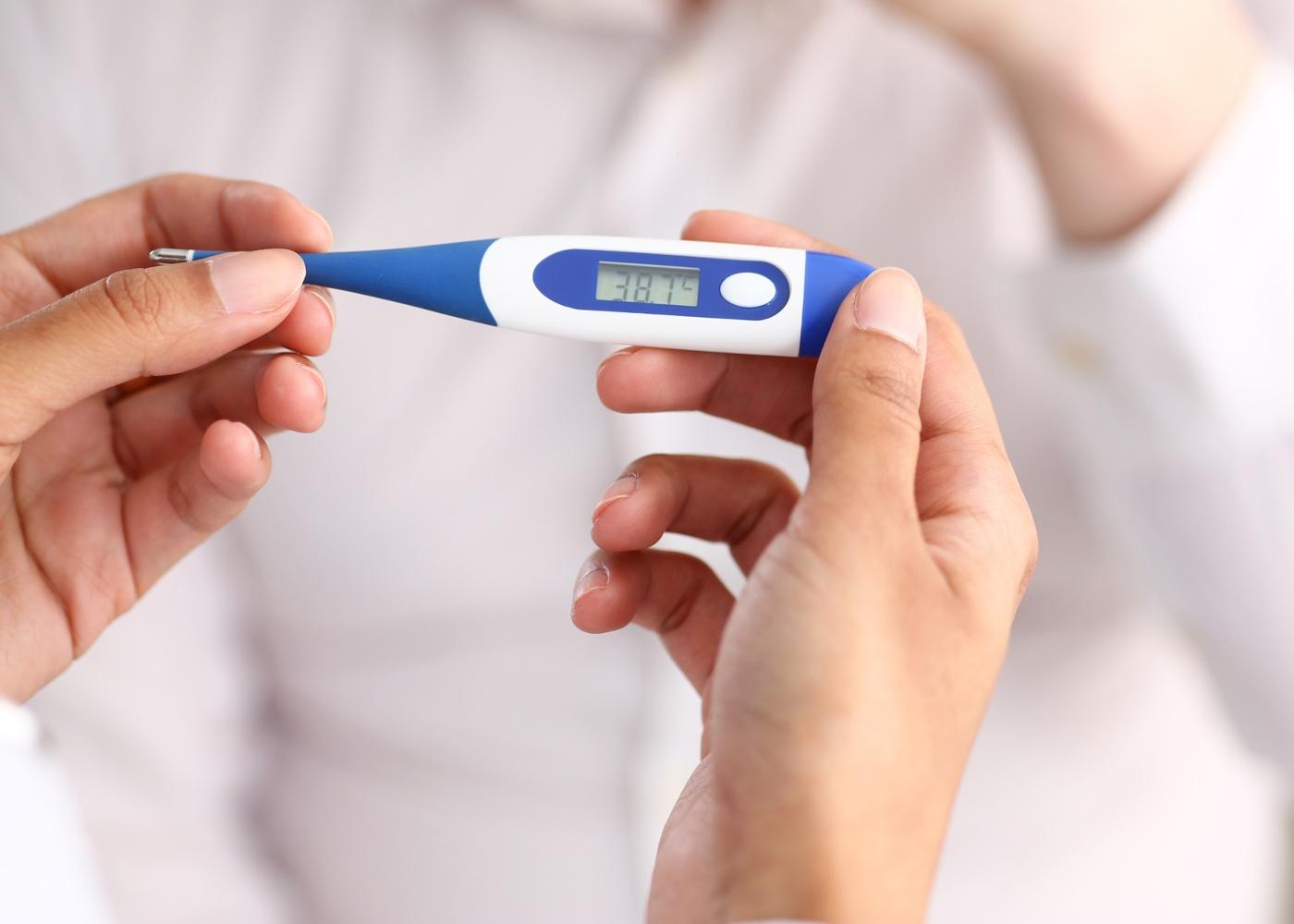 Mulher a verificar febre com termómetro