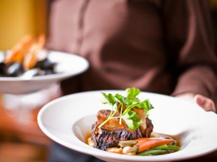 Abertura dos restaurantes: trabalhador da restauração com pratos de comida nas mãos