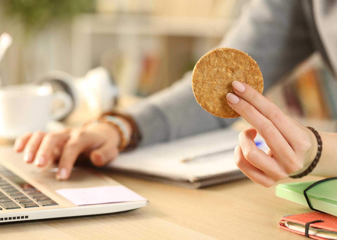 Alimentação na adolescência: adolescente a comer bolachas enquanto estuda