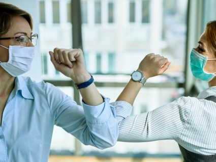 Como ultrapassar o medo de voltar a ver a família e amigos: duas amigas com máscara a cumprimentarem-se com os braços