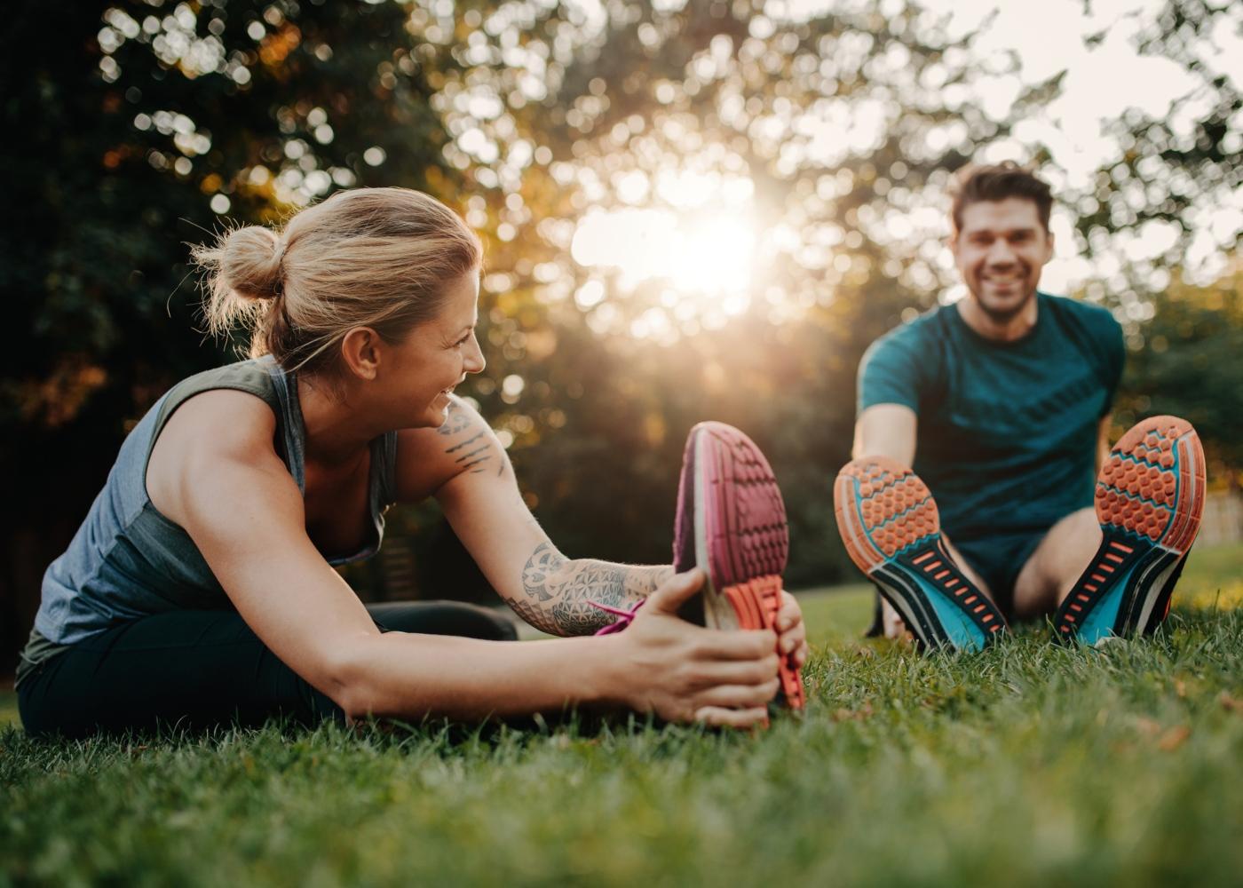 Casal a fazer alongamentos após treino no parque