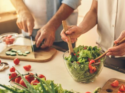 Dietas restritivas podem comprometer o sistema imunológico: casal a fazer uma salada para o almoço