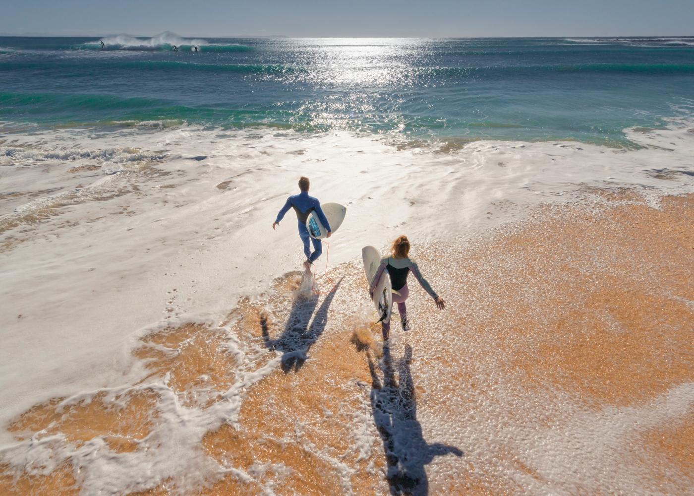 Casal a entrar no mar com pranchas de surf
