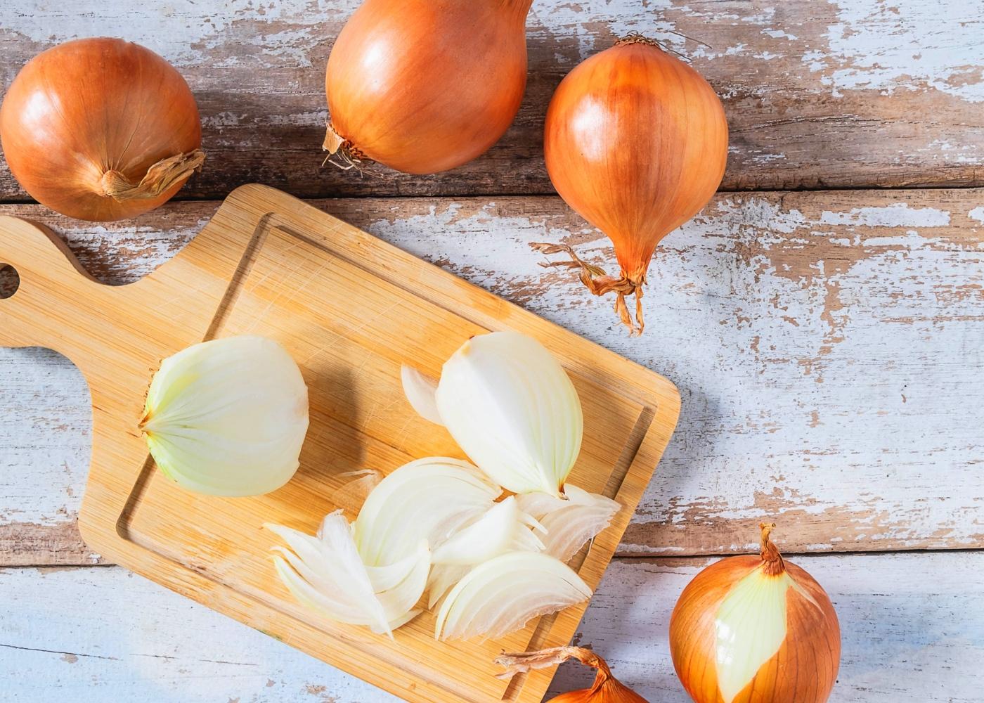 Cebolas inteiras e cebola cortada em tábua de madeira