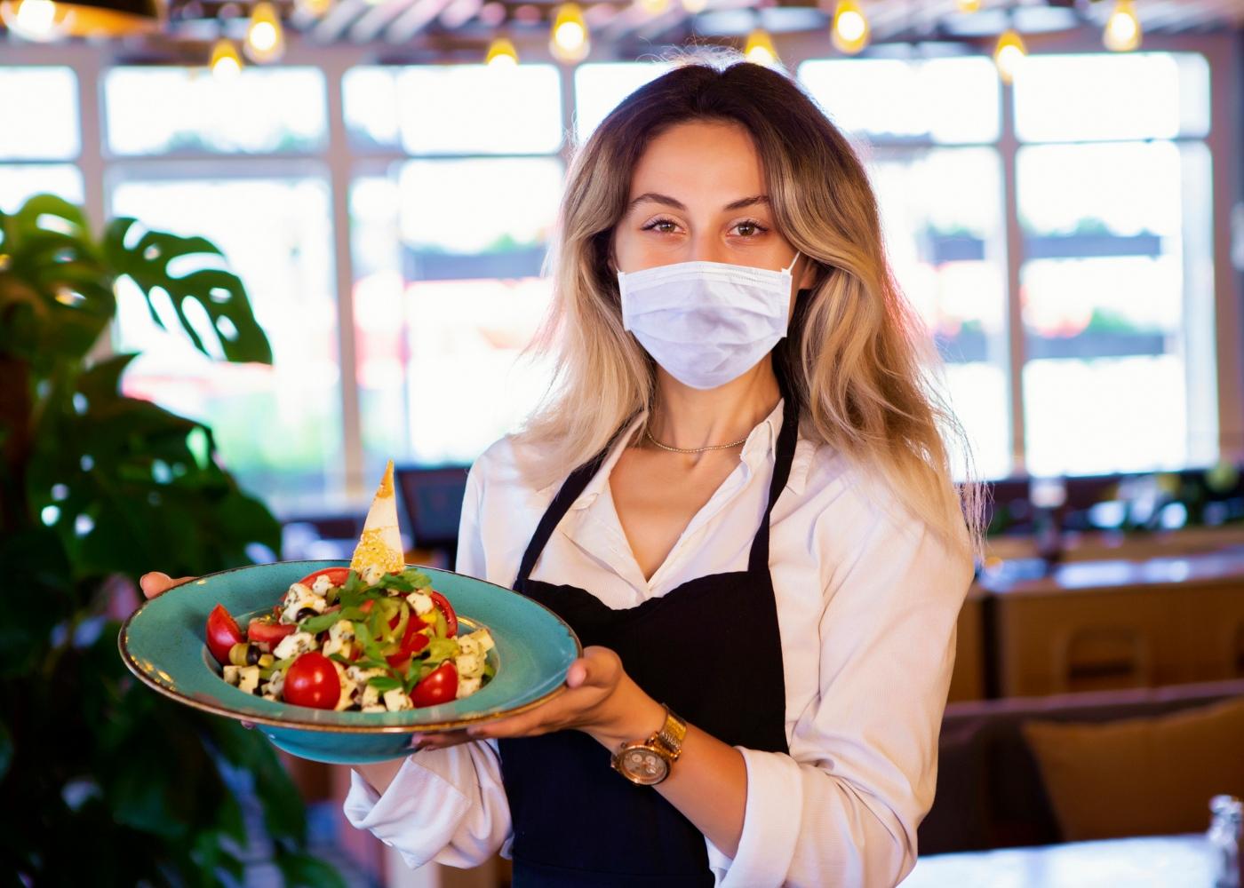 Funcionária de restaurante com máscara de proteção