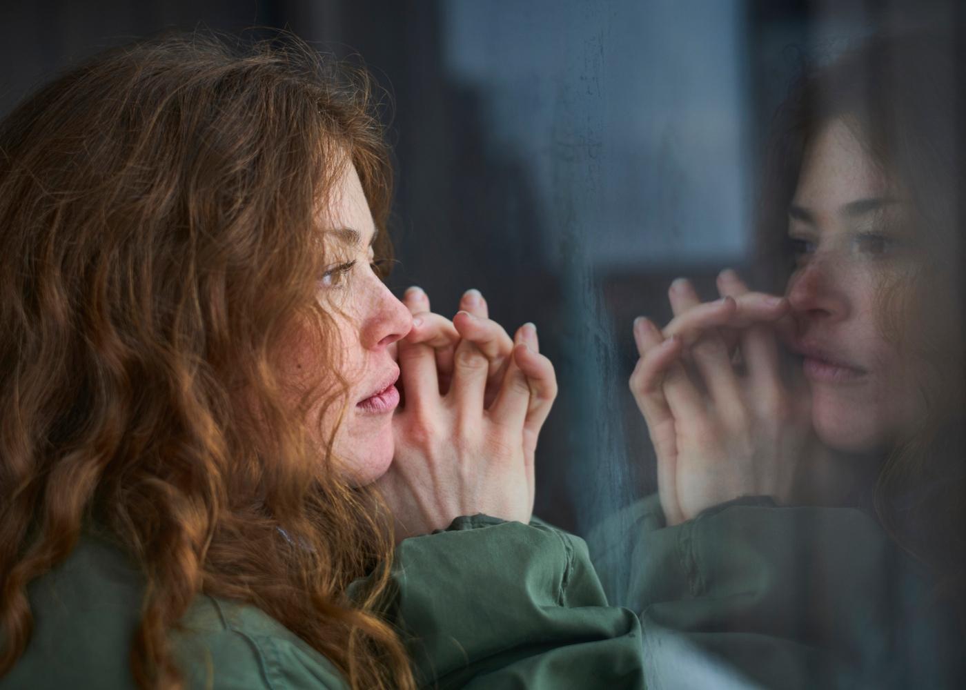 Gestão de stress e importância do exercício físico: mulher pensativa a olhar pela janela