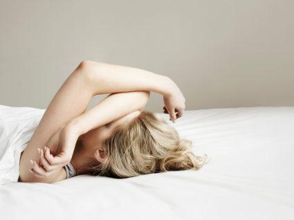 Importância do sono em tempos de pandemia: mulher deitada na cama a tentar dormir