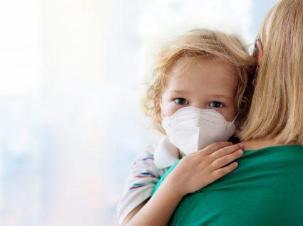 Imunidade nas criancas: menino com máscara de proteção no colo da mãe