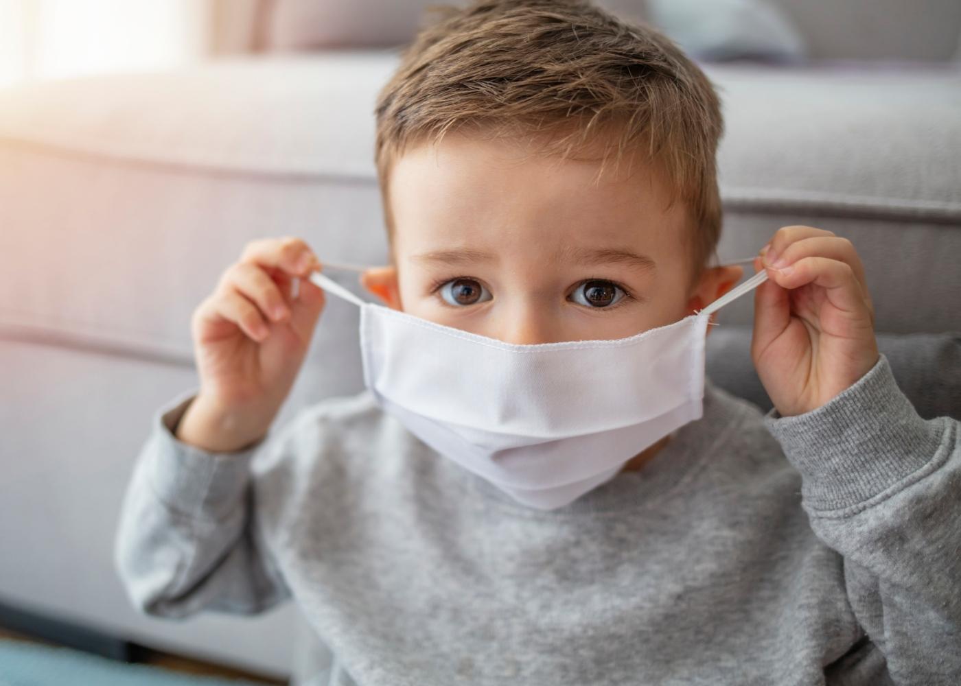 Menino com máscara de proteção em casa