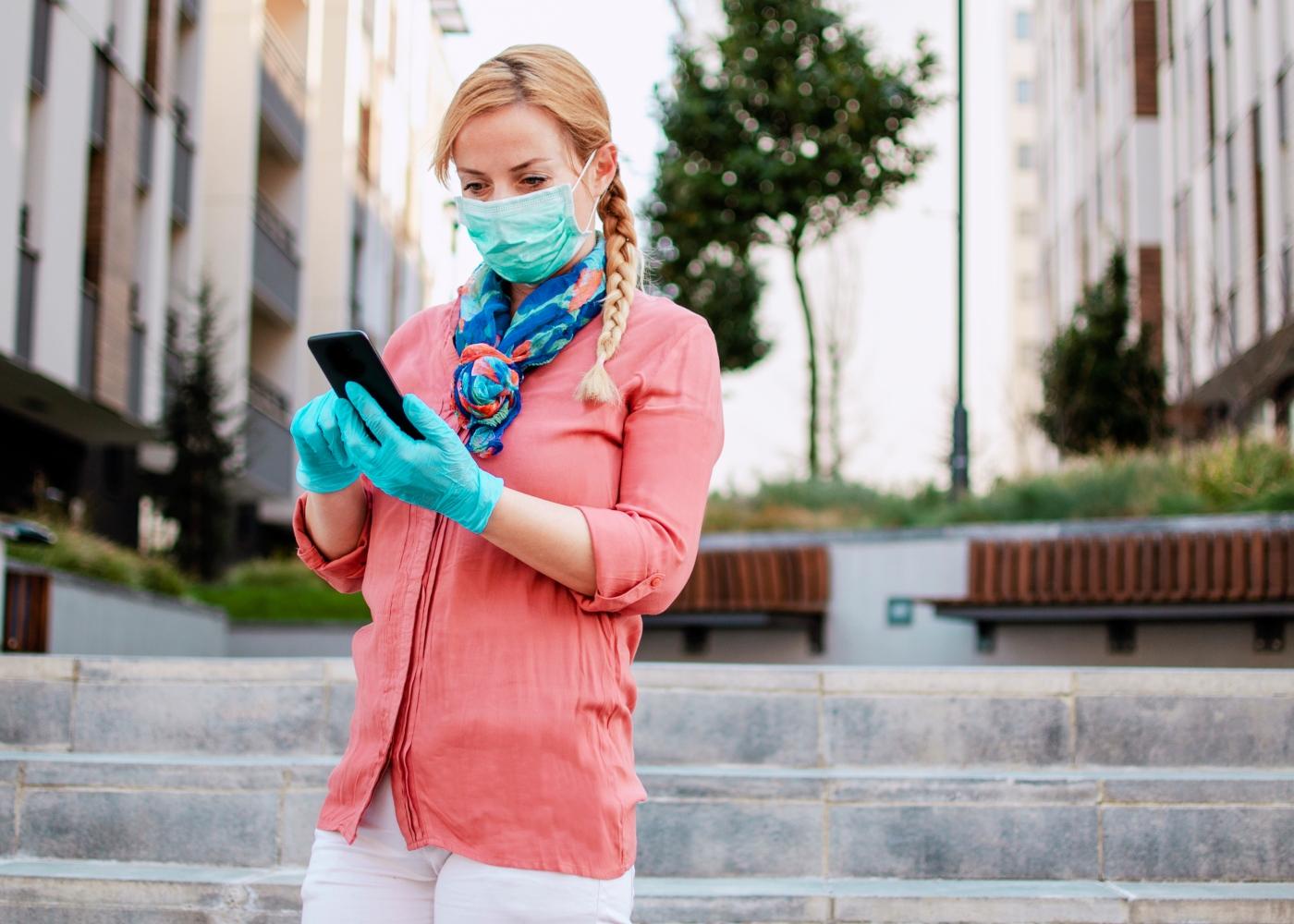 Mulher com máscara e luvas na via pública