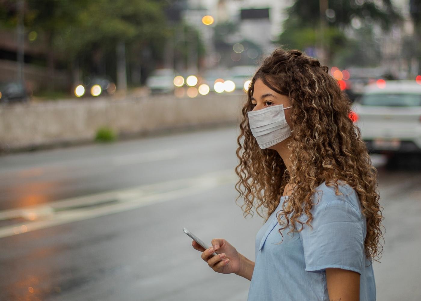 Mulher com máscara à espera de um Uber