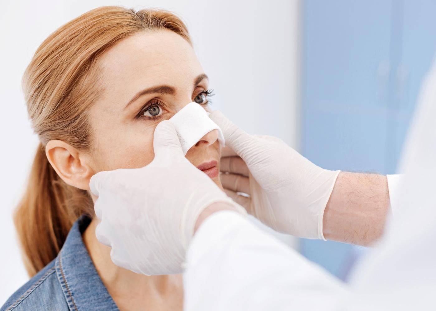 Mulher a fazer curativo após cirurgia nasal
