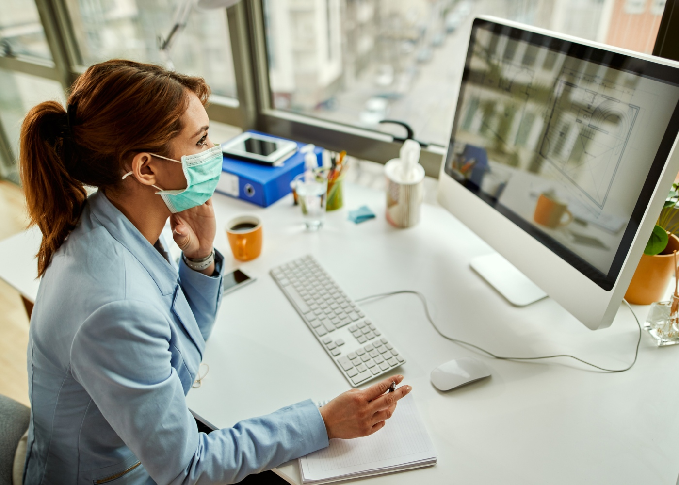 Mulher no escritório a trabalhar com máscara