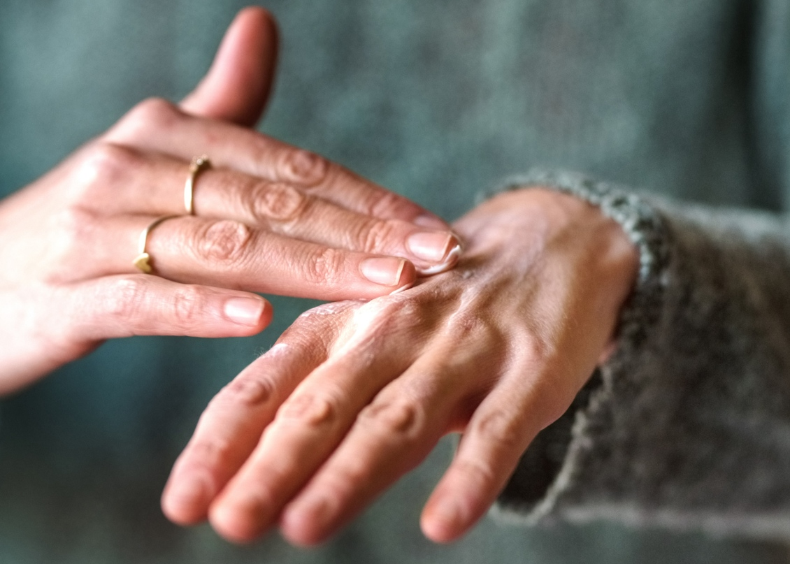 Mulher a hidratar as mãos