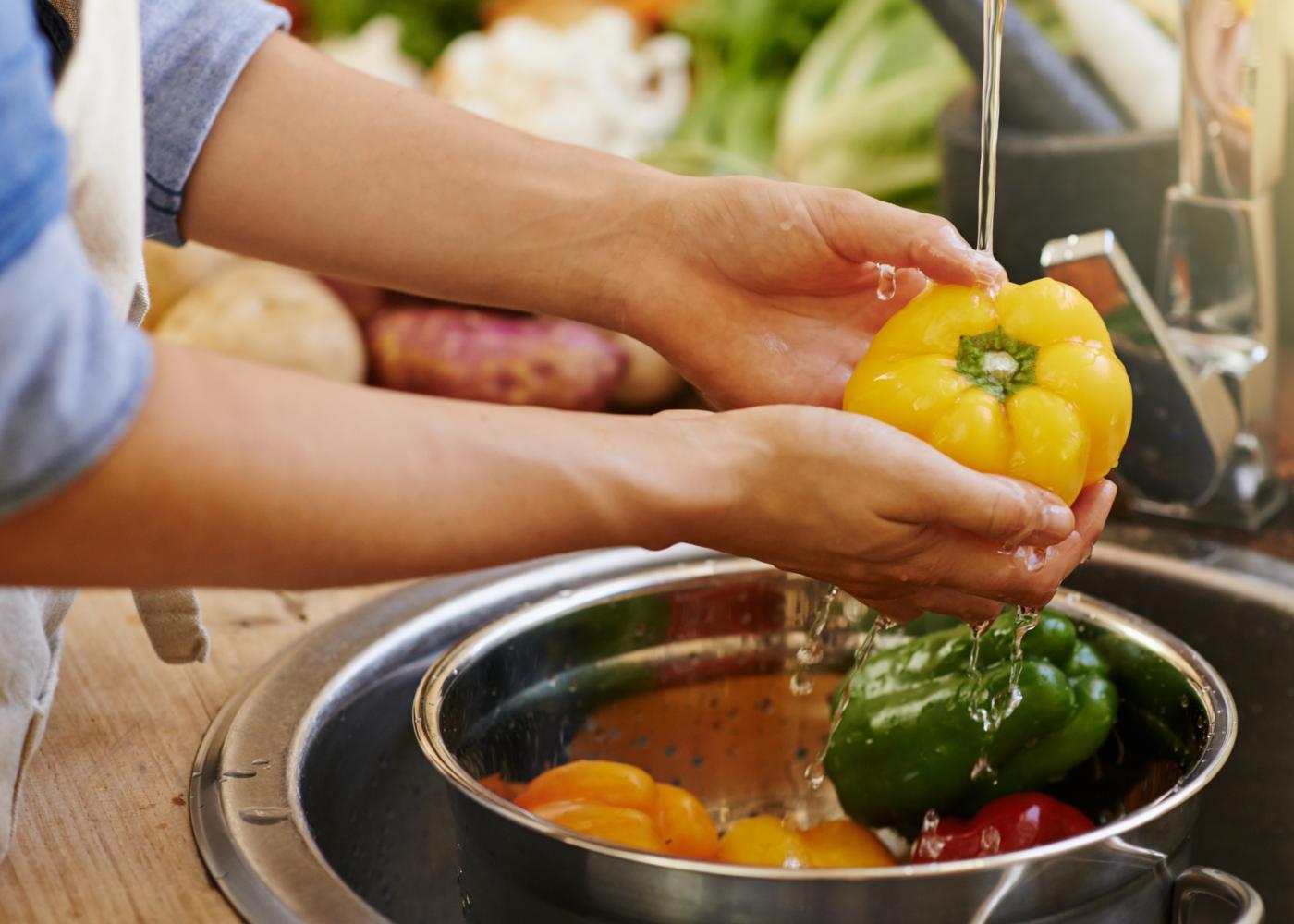 Higienizar e congelar alimentos frescos: mulher a lavar alimentos