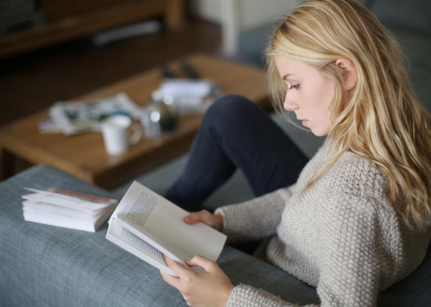 Mulher sentada no sofá a ler um livro