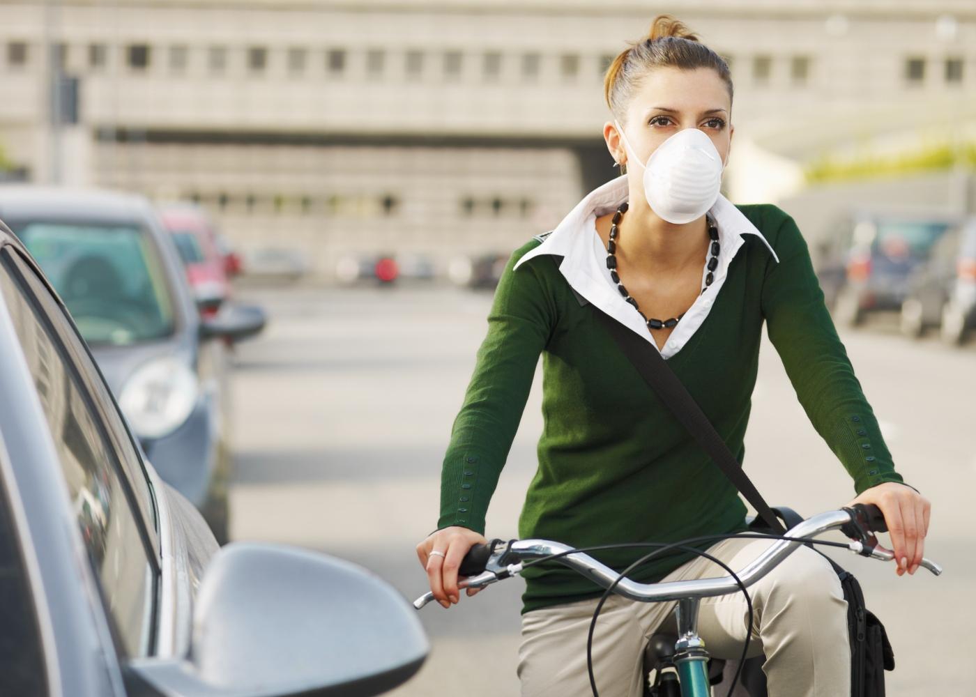 Mulher com máscara a andar de bicicleta pela cidade