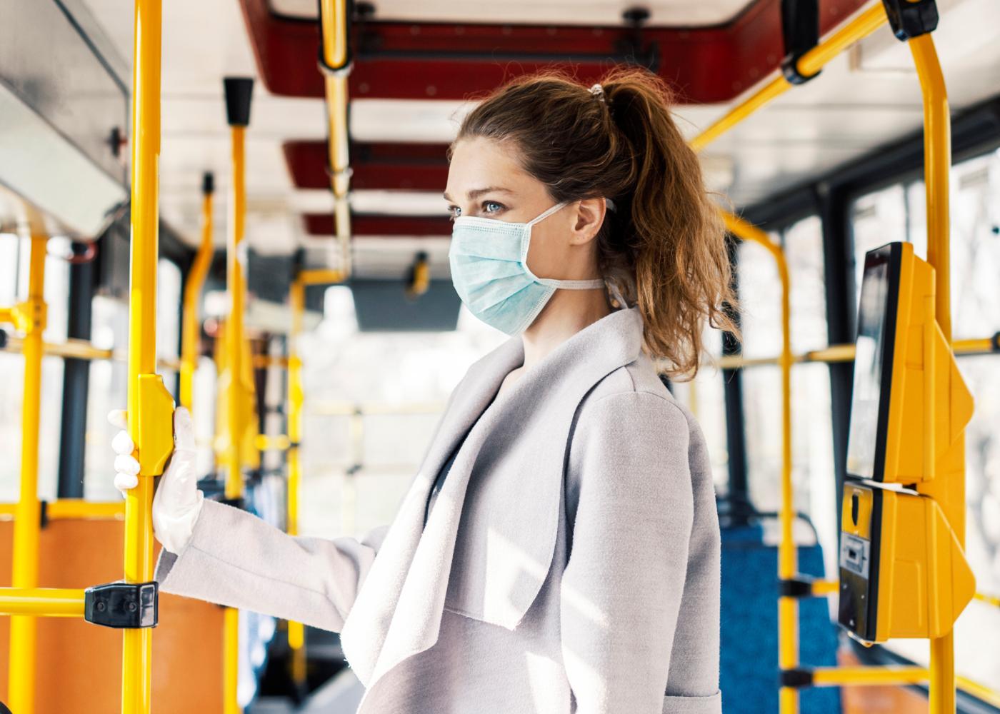Comportamento socialmente responsável: mulher com máscara em autocarro