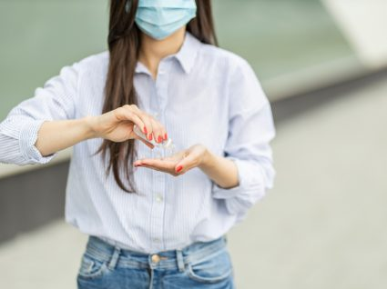 Regras para sair de casa em segurança: mulher a desinfetar as mãos