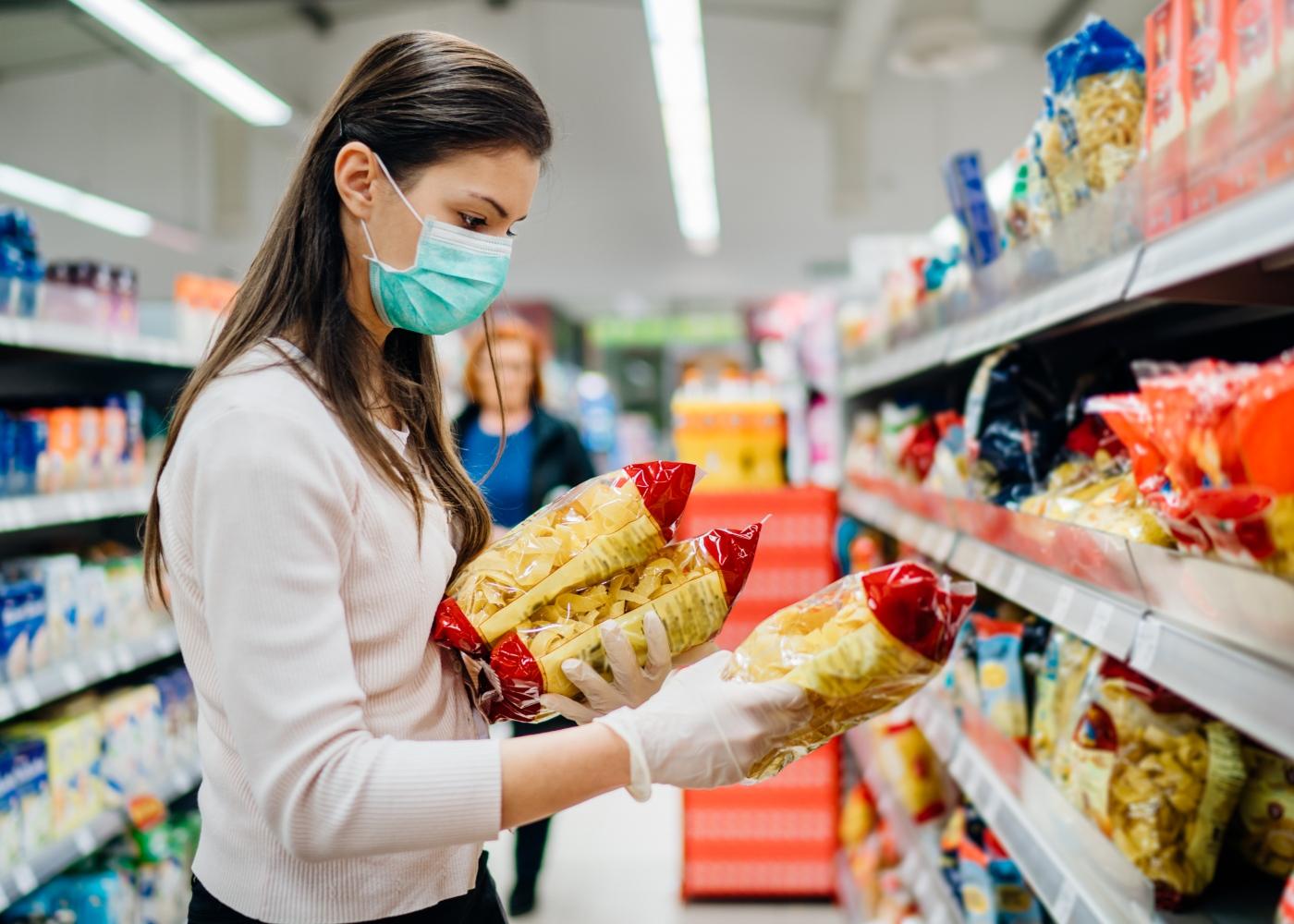 Mulher no supermercado com máscara e luvas