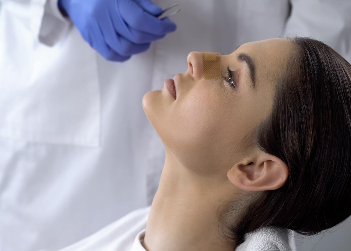 Mulher a fazer curativo após ter feito cirurgia nasal