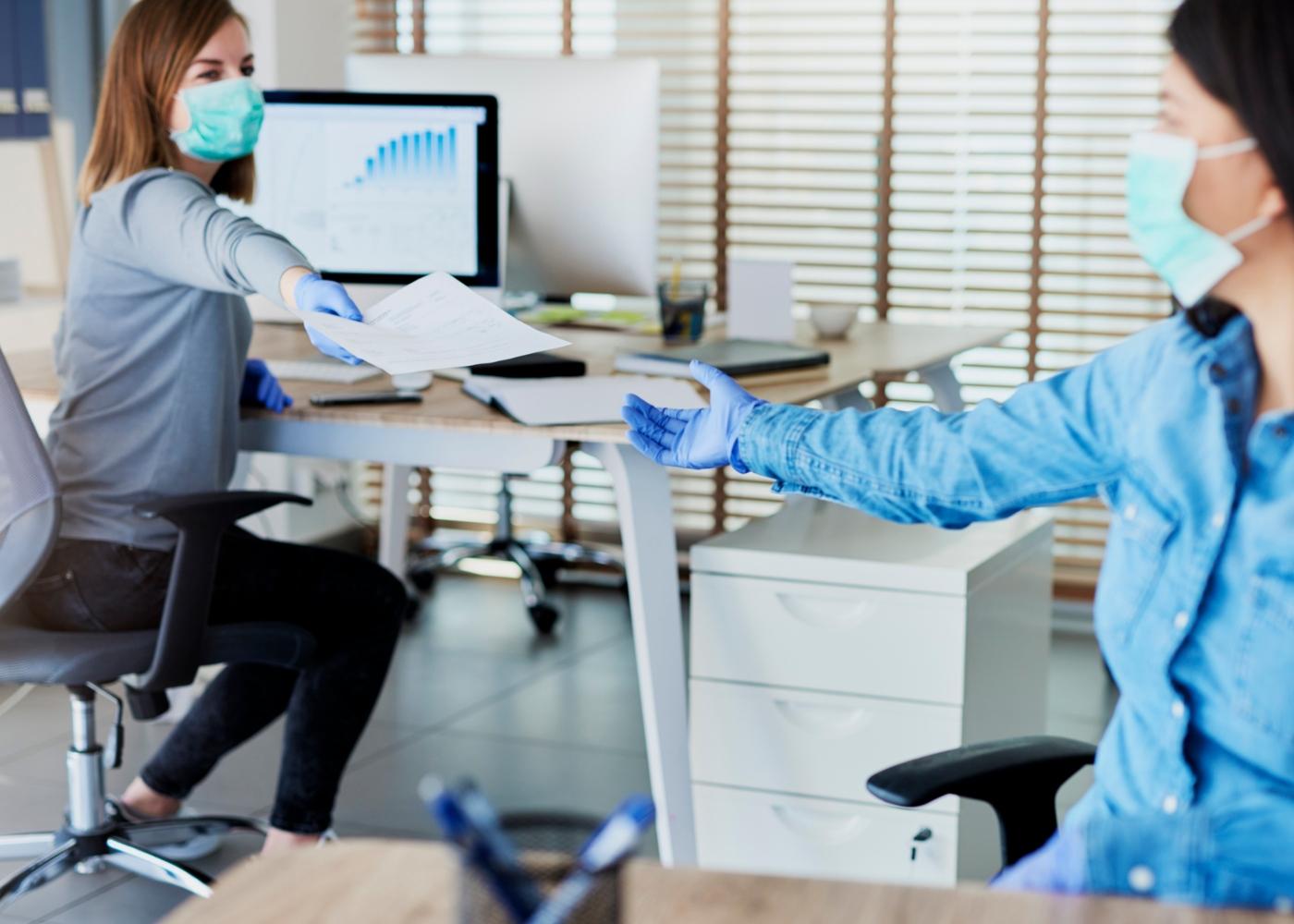 Comportamento socialmente responsável: funcionárias de empresa a respeitar regras sanitárias