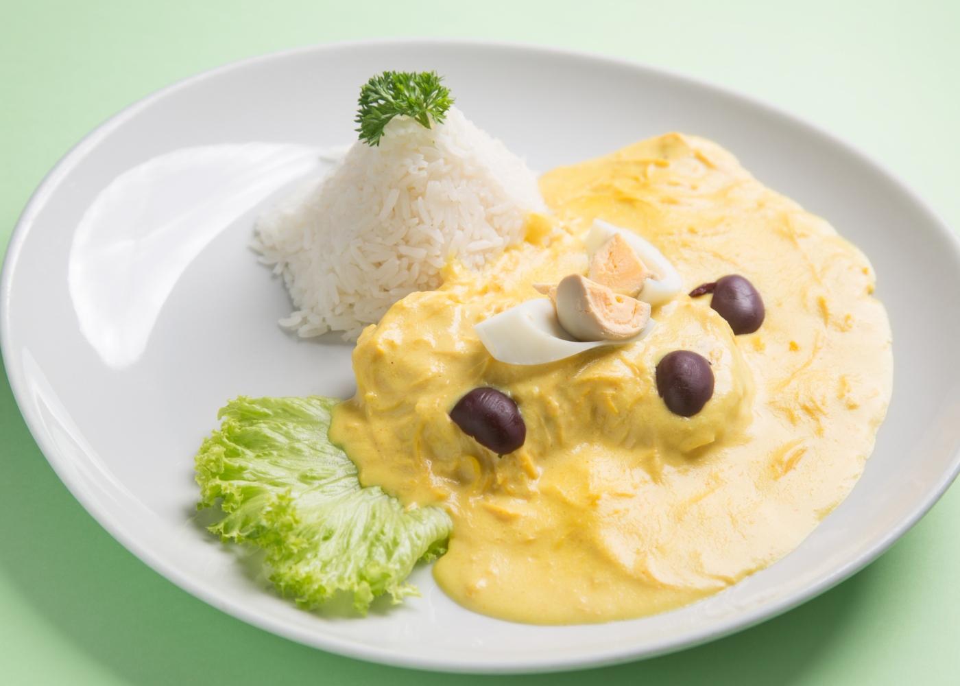 Aji de gallina servido num prato com arroz