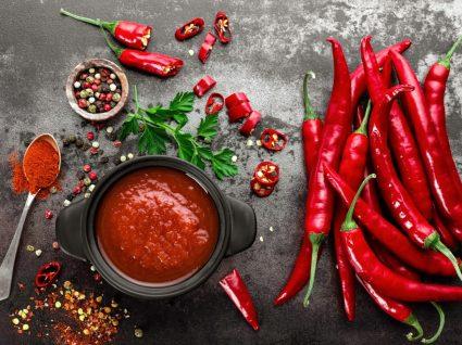 Alimentos que aceleram o metabolismo: malagueta fresca e em pó em cima de mesa