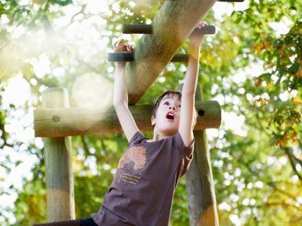 Atividades físicas para fazer com crianças ao ar livre: menino a brincar à escalada no parque
