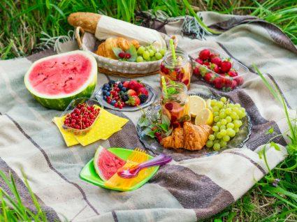 como fazer um piquenique saudável: variedade de frutas e outros alimentos numa toalha no parque