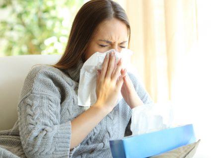 COVID-19, constipação e alergia: mulher a assoar-se