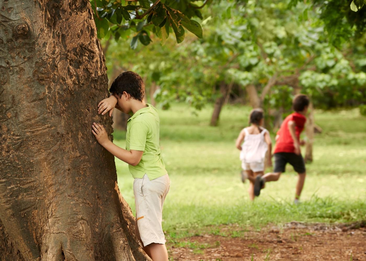 Crianças a jogar às escondidas no parque