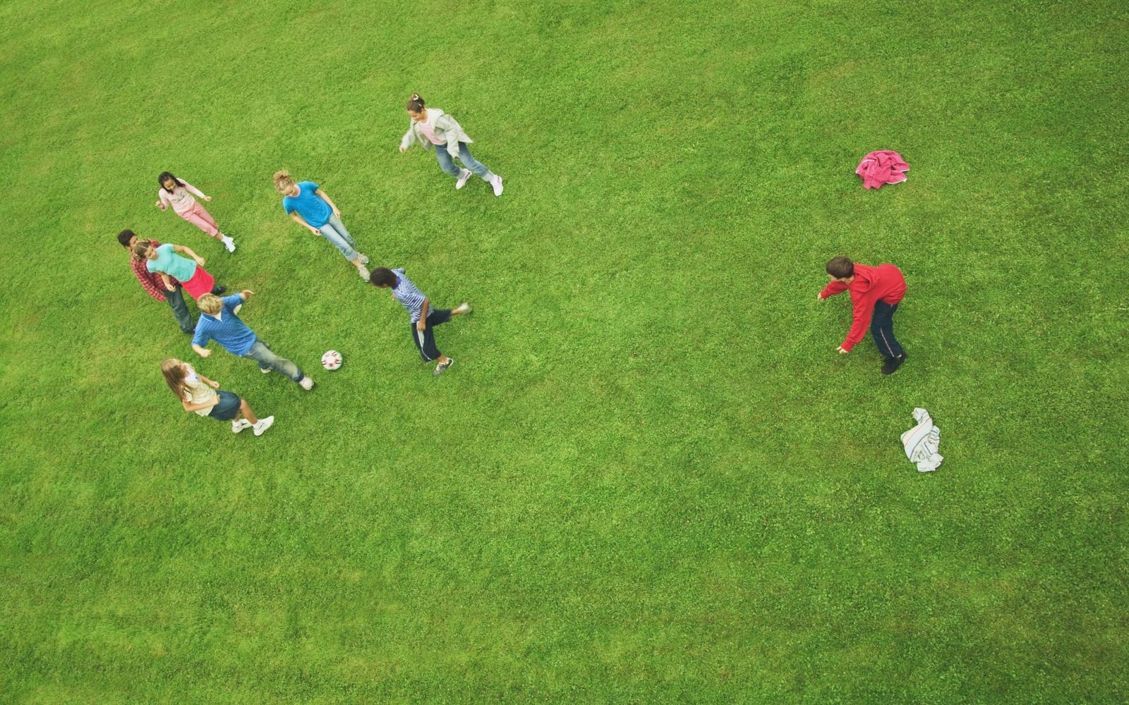 Grupo de crianças a jogar futebol