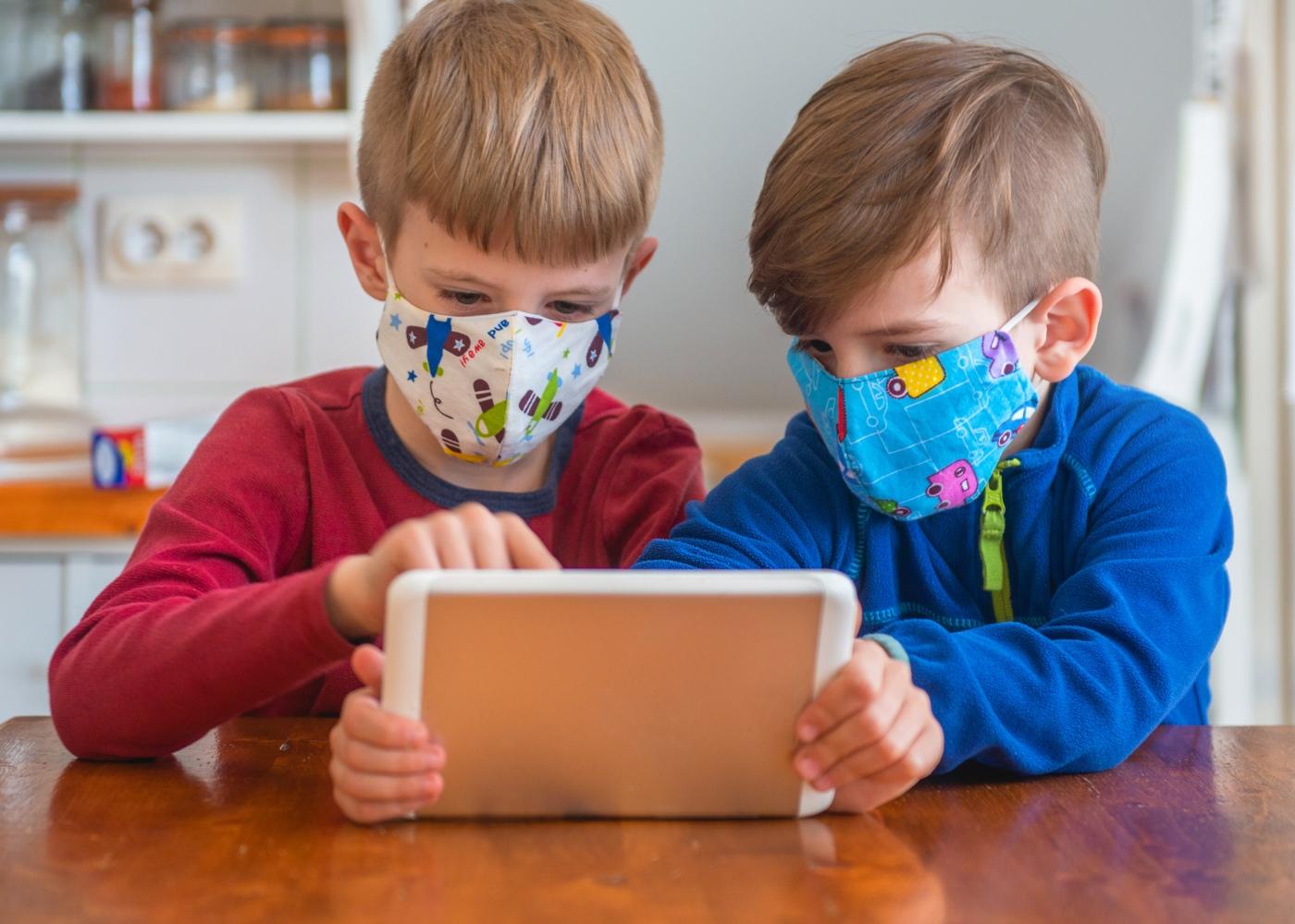 Crianças com máscara a jogar num tablet