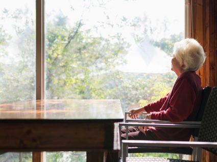 Desnutrição no idosa: idosa sentada numa mesa a olhar pela janela