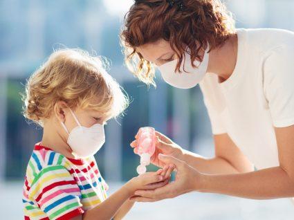Regras nos ATL: educadora a desinfetar mãos de criança
