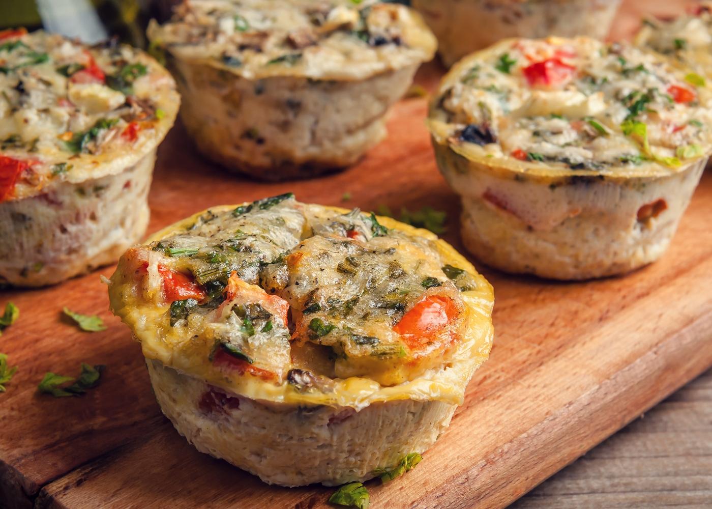 Egg muffins de legumes em cima de tábua de madeira