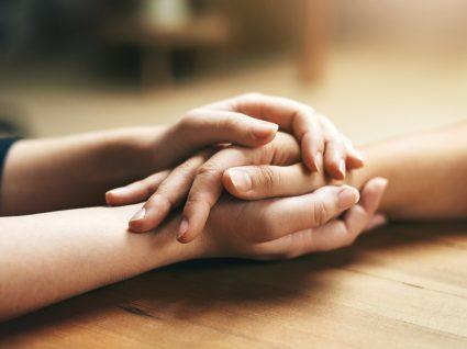 Pessoa a segurar na mão de outra num momento de empatia