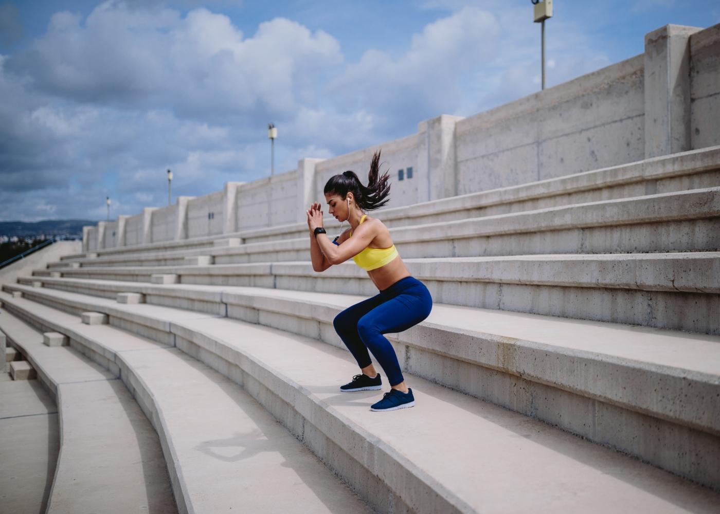 Mulher a fazer exercícios de agachamento ao ar livre