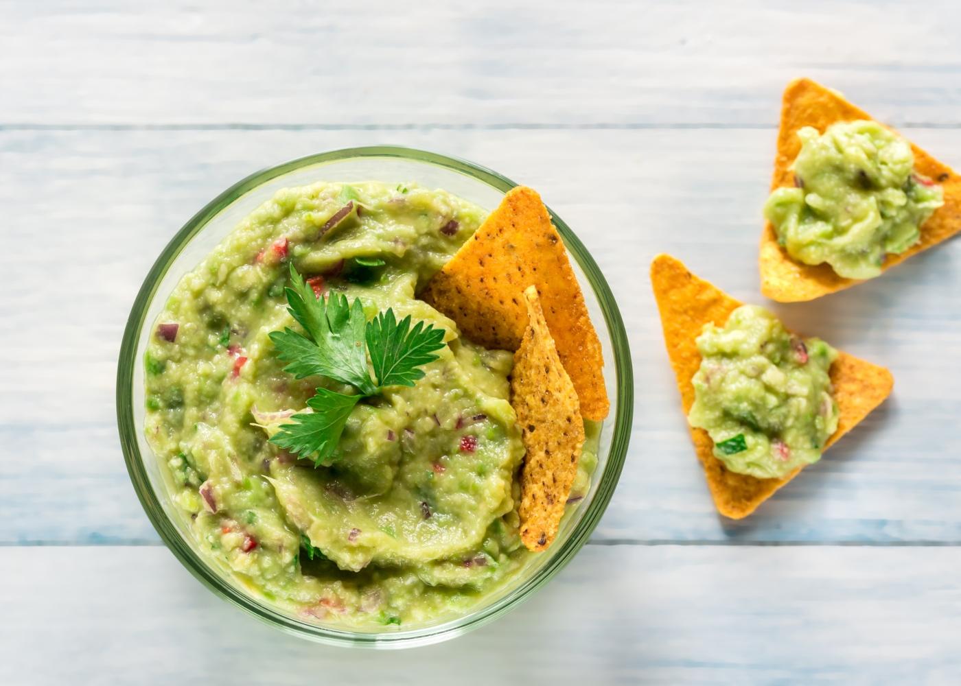Taça de vidro com guacamole e tortilhas de milho