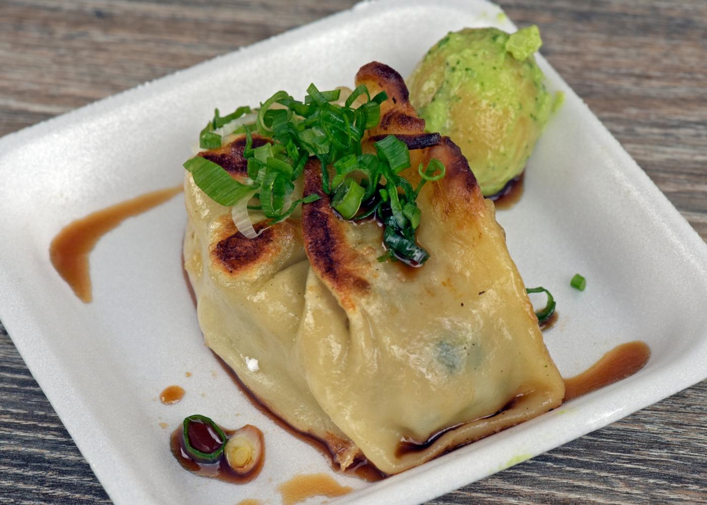 Guioza de carne servida num prato com wasabi
