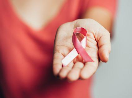 Mulher com laço cor-de-rosa da Liga Portuguesa Contra o Cancro na mão