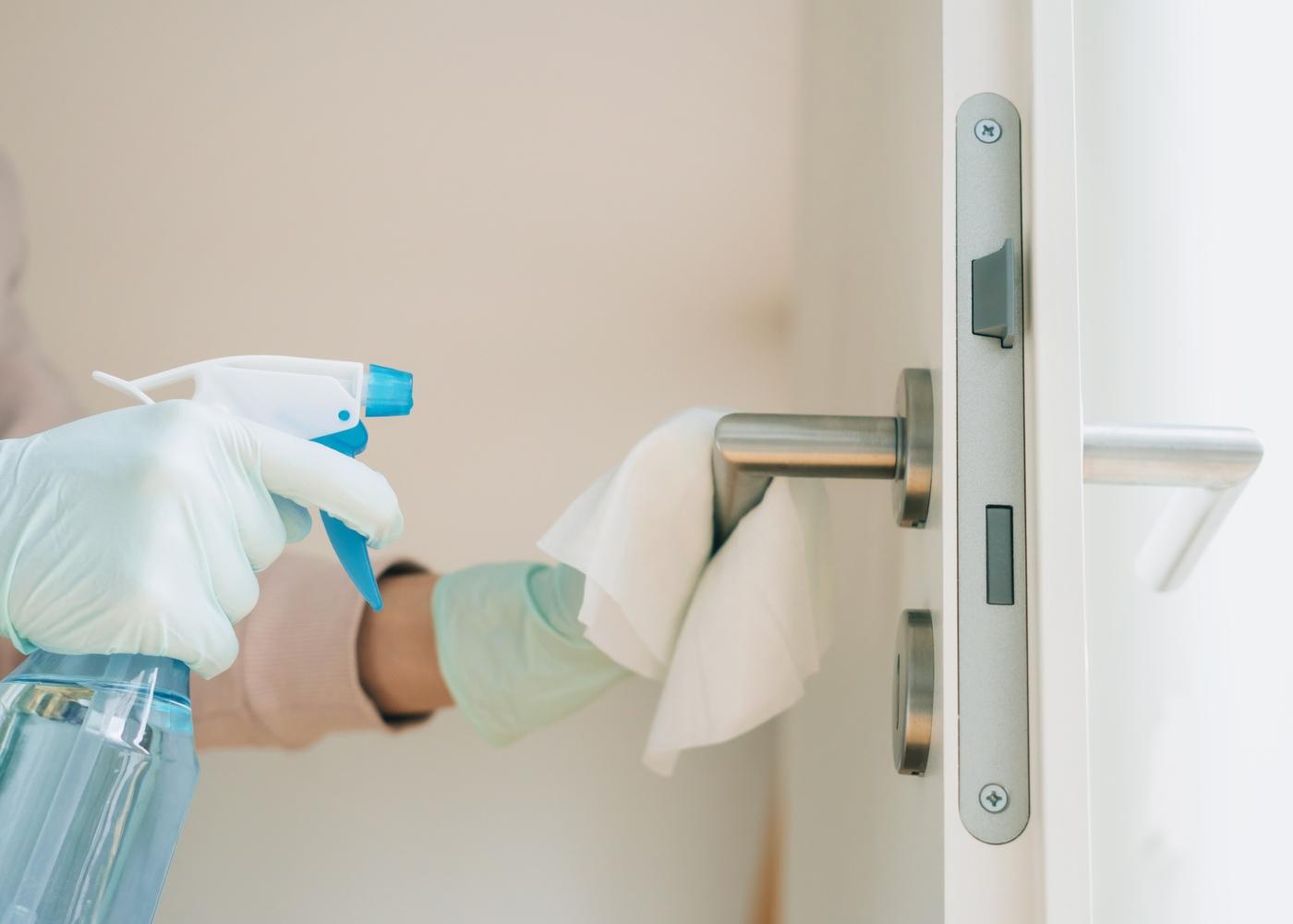Senhora da limpeza de uma escola a desinfetar puxadores de portas