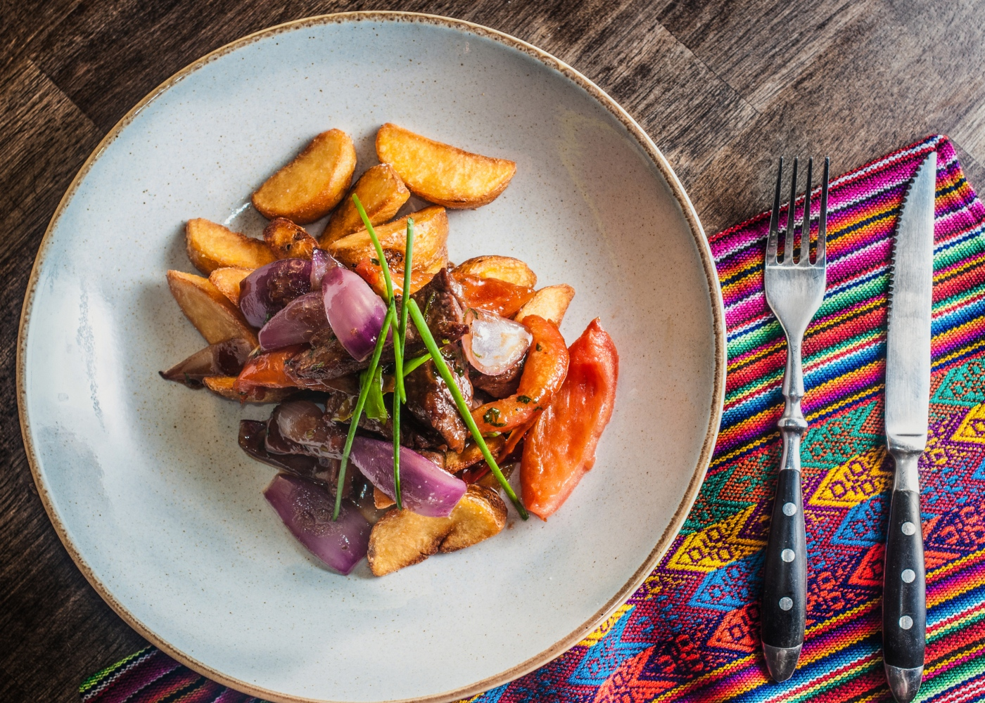 Lomo saltado servido num prato acompanhado com batata e salada