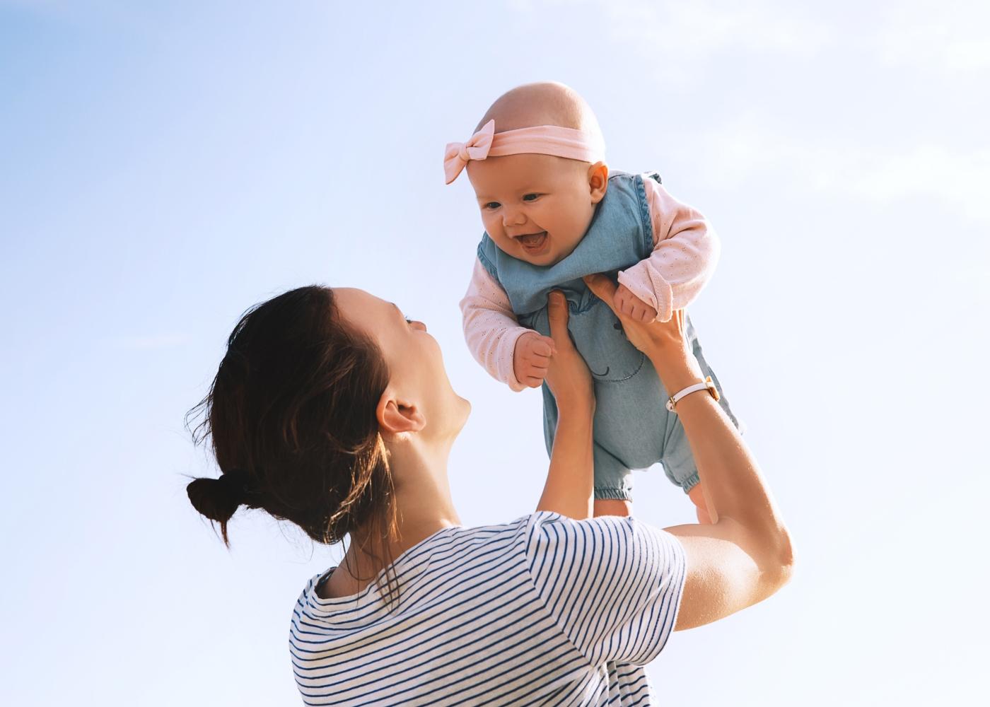 Mãe com bebé ao colo na praia
