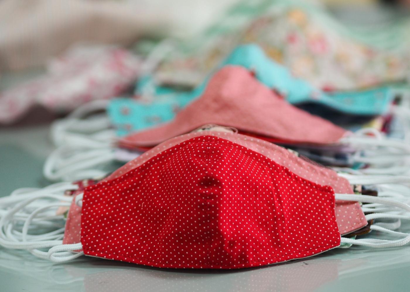 Variedade de máscaras de tecido em cima de uma mesa