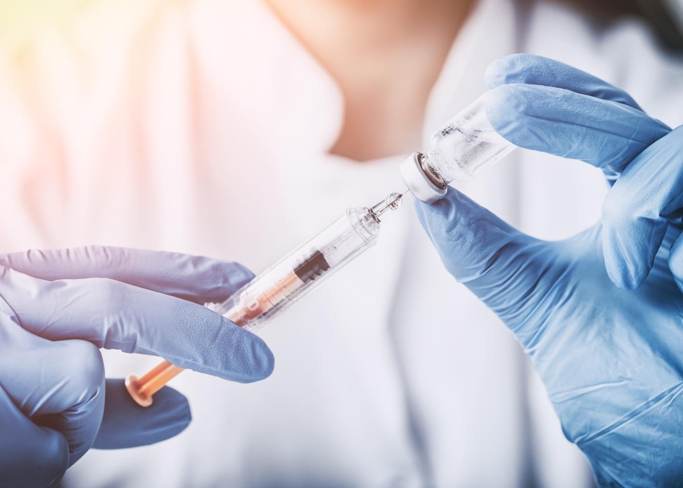 Médica a dar medicamento a doente internado por via intravenosa