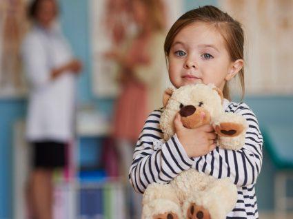 Síndrome multissistémica inflamatória pediátrica: menina abraçada a peluche no hospital