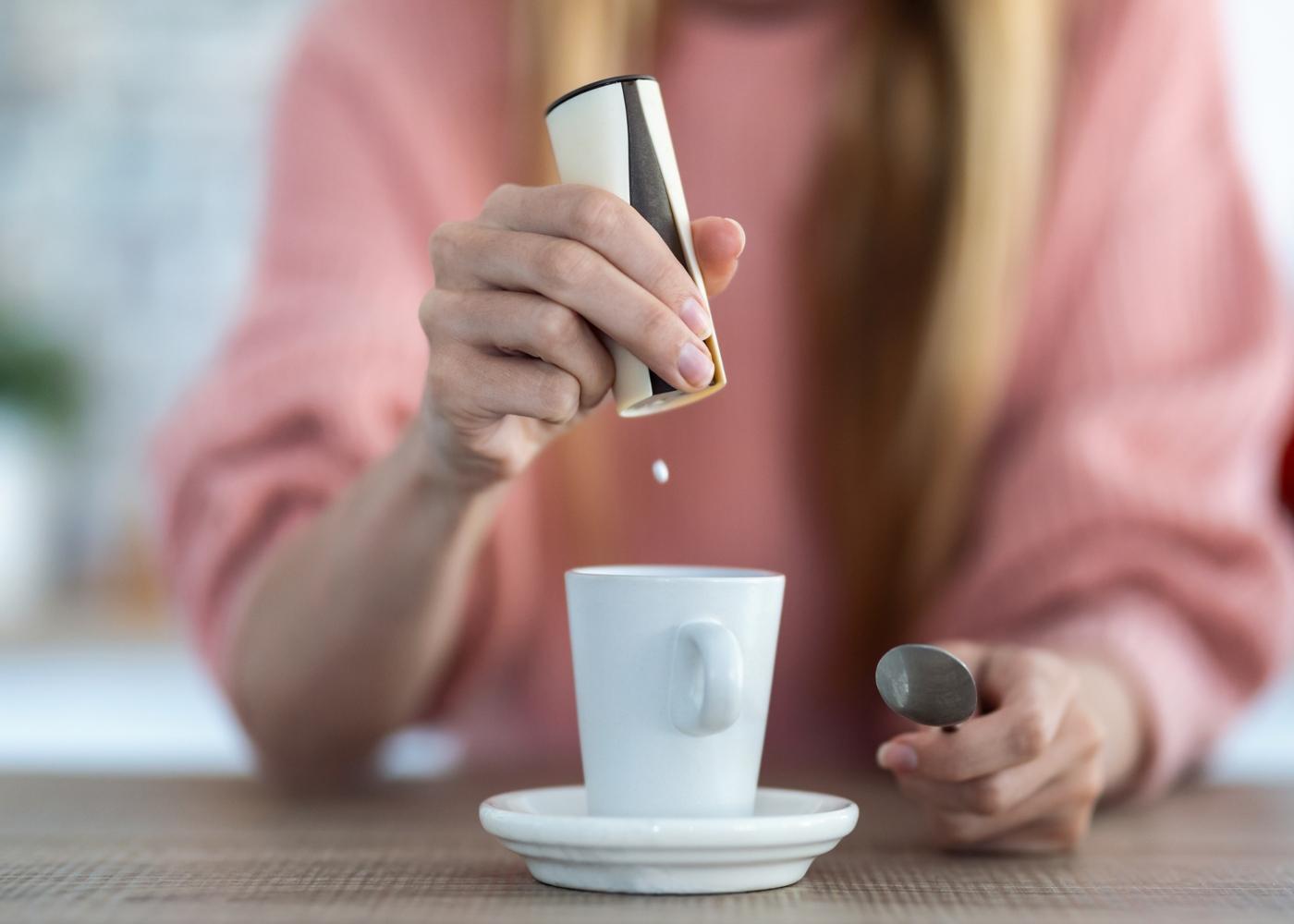 Mulher a colocar adoçante no café
