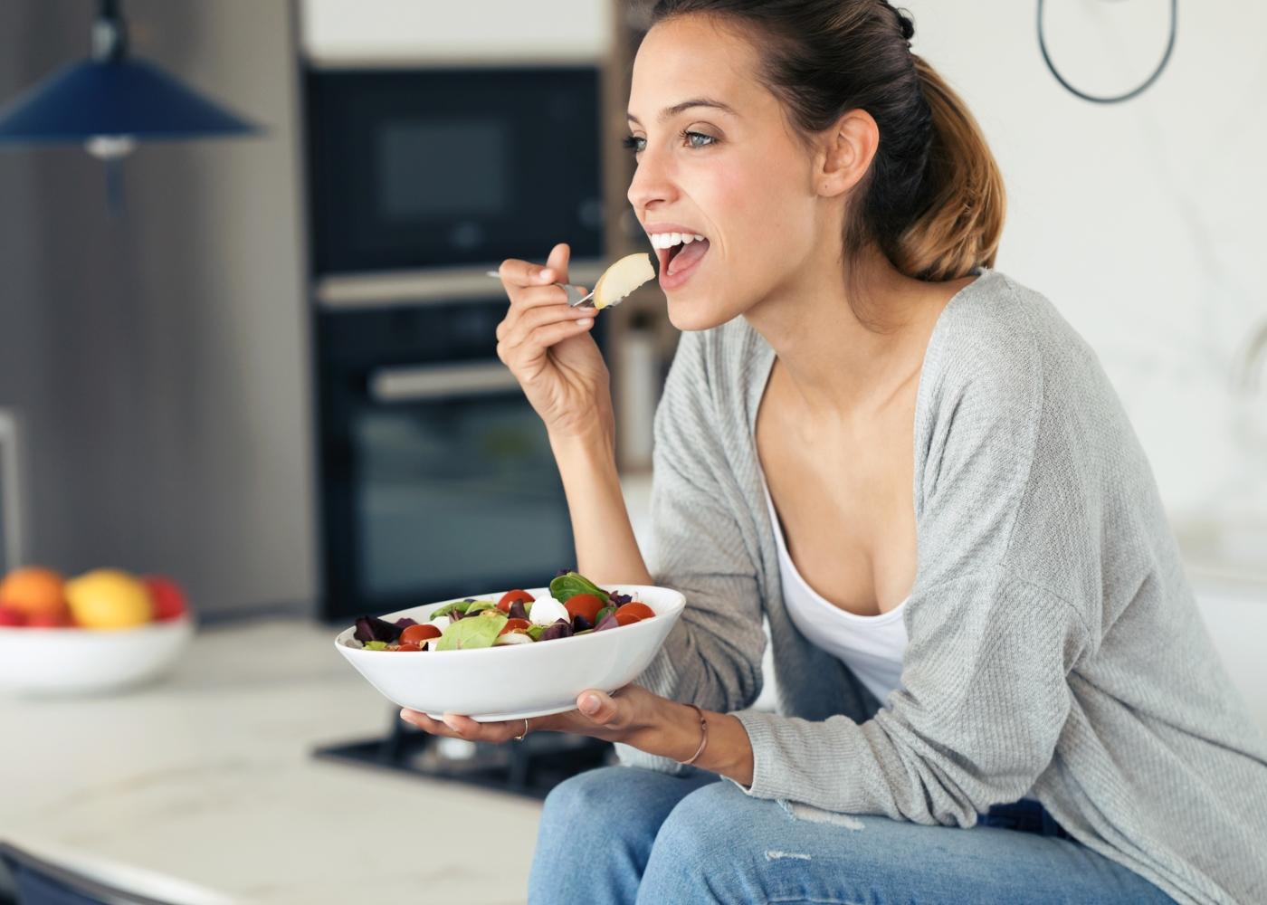Mulher sentada no balcão da cozinha a comer uma salada
